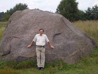"Dr. Rimantas Petrosius, University of Vilnius; geophysicist, in front of the ""Devil's Stone"" located in Northern vicinity of the Švendubrė village. (c) Dr. Rimantas Petrosius, 2011"